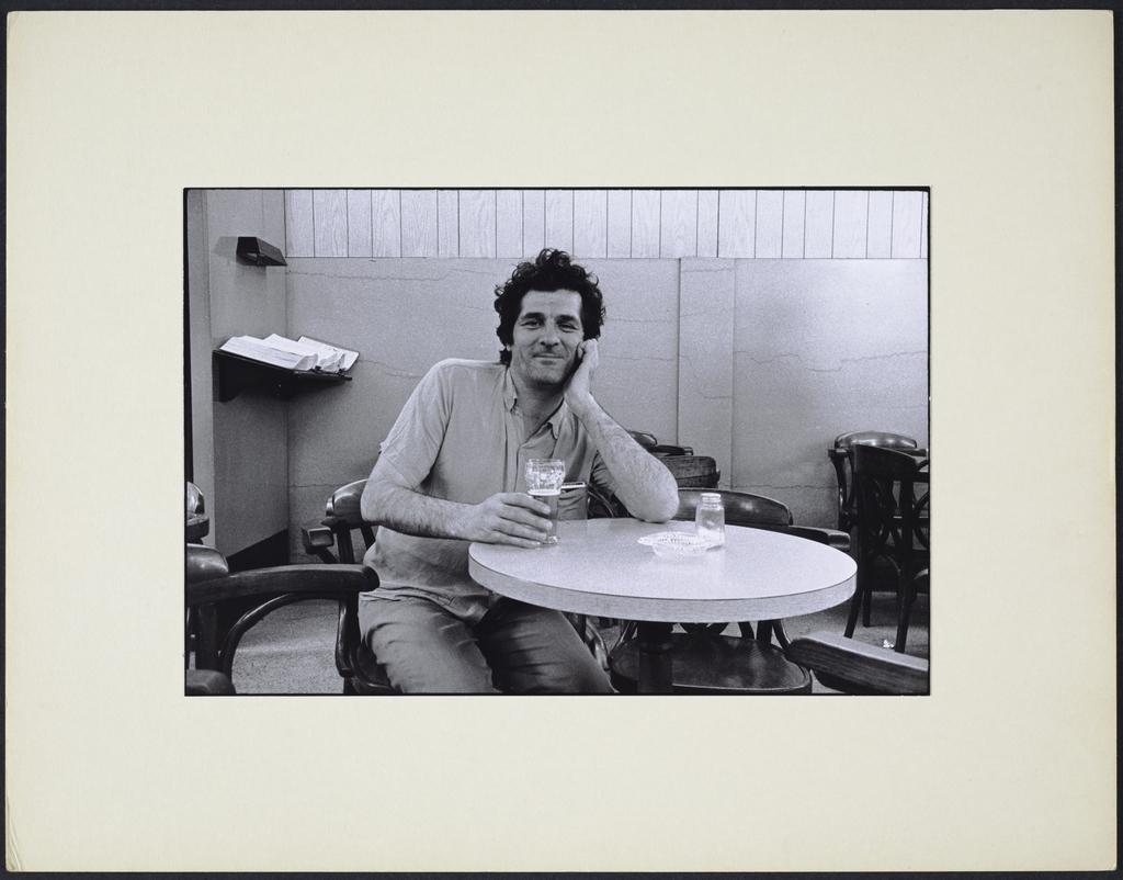 Un gars avec un verre de bière, accoudé sur la table, de la série « La Taverne »