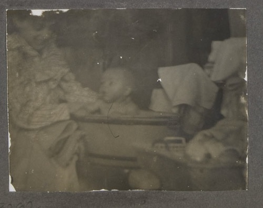 Femme donnant le bain à son enfant, d'un album de famille amateur